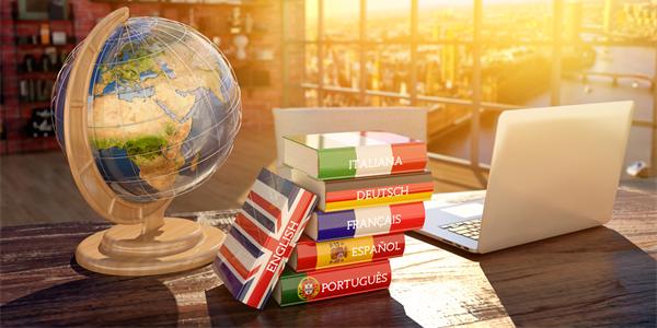 o que fazer na quarentena - mesa de madeira com pilha de livros, cada livro tem a bandeira de um país diferente, ao lado temos o globo terrestre. ao fundo luz do entardecer.